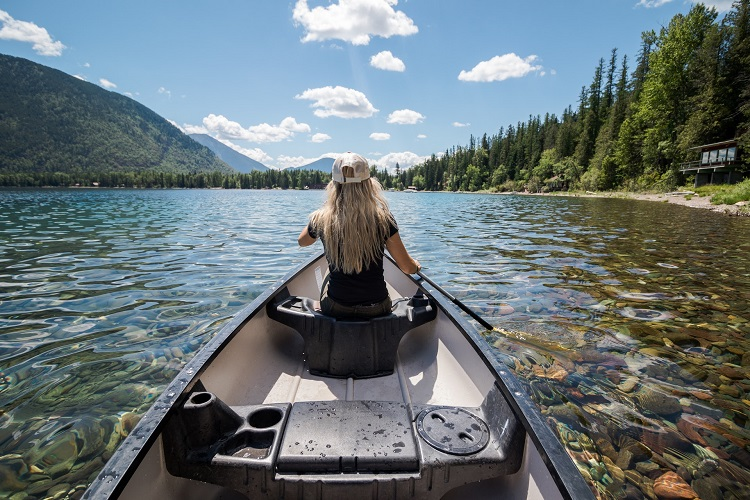 shot from inside a canoe of woman rowing on beautiful clear river water - sobriety