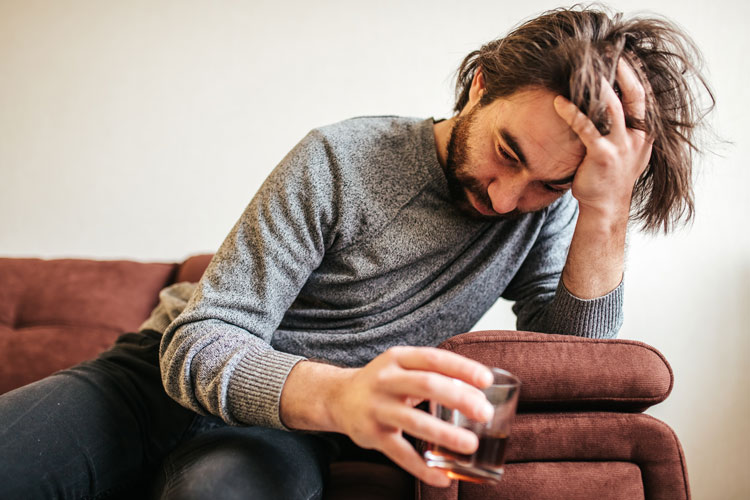 middle age man with long hair and a beard looking defeated, holding a glass of liquor while on the couch at home - addiction signs